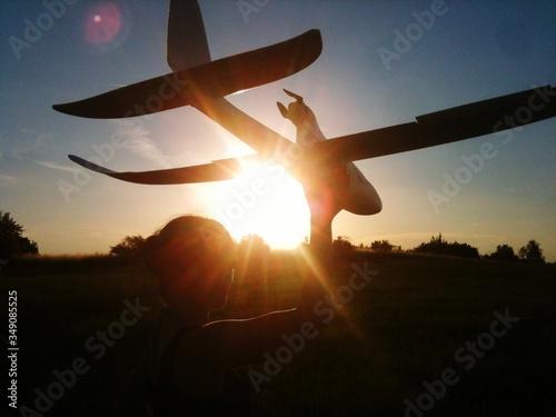 Fényképezés Back Lit Woman Holding Aloft Toy Airplane On Field