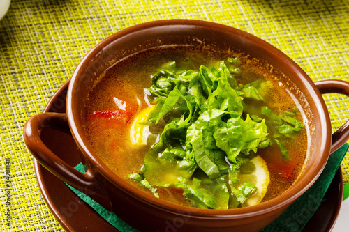 Fototapeta Soup with salad in a clay pot on the table, lunch obraz