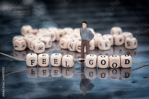 Miniature model of man and wooden cubes with feel good inscription strung on a thread on reflective table with heap of other cubes behind.