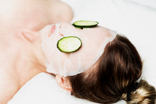 A Young Woman Lies With A Tissue Beauty Mask On Her Face And With Slices Of Cucumber In Her Eyes. Personal Care. Close-up.