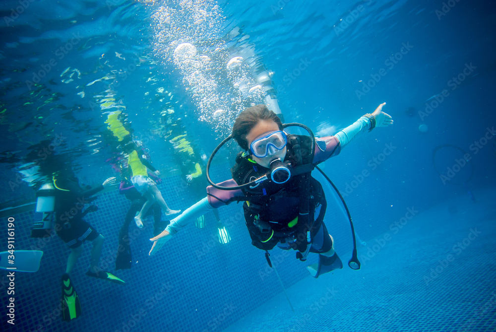 Fototapeta Underwater, a 10 year old boy diving in a pool with fun. This is diving for children.