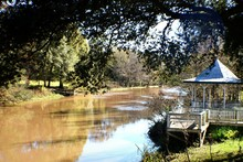 Gazebo By River Against Trees