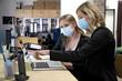 canvas print picture - Zwei Büroangestellte mit Mund- und Nasenschutz arbeiten gemeinsam am Schreibtisch