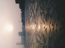 Frozen River In City At Sunset