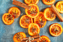 Slices Of Dried Oranges Or Tangerines With Anise And Cinnamon, On A Blue Background. Vegetarianism And Healthy Eating