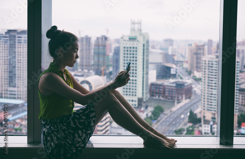 Fototapeta Woman using mobile phone relaxing by condo window at home or office room silhouette. Business woman at work pensive looking at cellphone social media app. Mental health online addiction concept. obraz