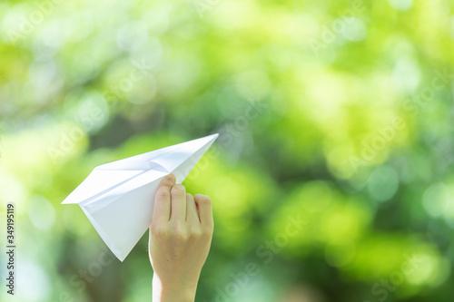 Fotografiet 手作りの紙飛行機を持つ若い女性女性