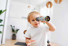 Little Boy Looking Into Kaleidoscope. Blurred. Focus On A Boy. At Home