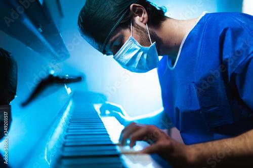 Fotografia Medico pianista si rilassa suonando il pianoforte dopo il turno in ospedale