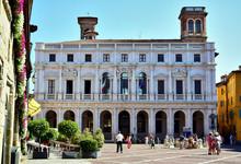 Bergamo / Lombardy, Italy - Biblioteca Civica Angelo Mai, Occupy The Palazzo Nuovo Di Bergamo On The Piazza Vecchia, A White Building, People Are Walking In The Square In Front Of It.