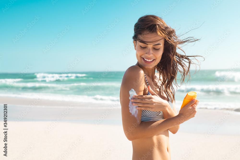 Fototapeta Woman in bikini applying sunscreen