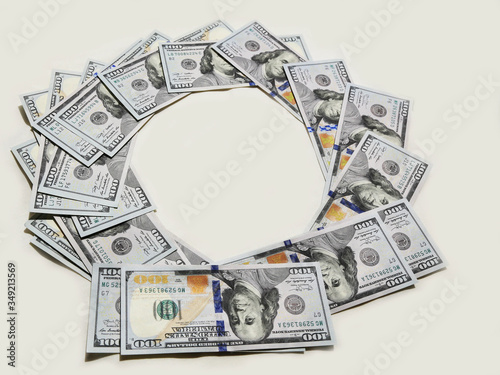 Hundred-dollar bills are laid out exactly in a circle on a white background Canvas-taulu
