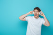 excited guy touching wireless headphones and looking away on blue background