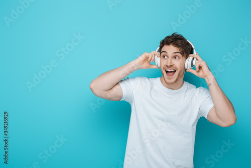 Fotografía excited guy touching wireless headphones and looking away on blue background