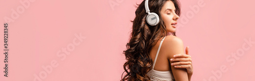 Horizontal crop of sexy girl in headphones listening music with closed eyes isolated on pink