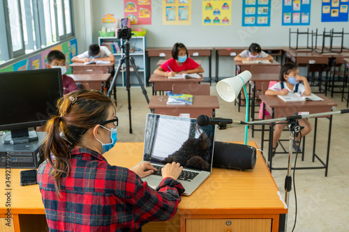 Teacher wearing protective mask to Protect Against Covid-19,Group of school kids with teacher sitting in classroom online and raising hands,Elementary school,Learning and people concept Fototapet