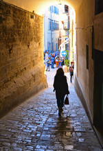Woman Walks In Narrow Street Near Corso Cavour Street With People In Old Historic Center In Medieval Town Citta Di Castello Near Perugia In Umbria, Italy