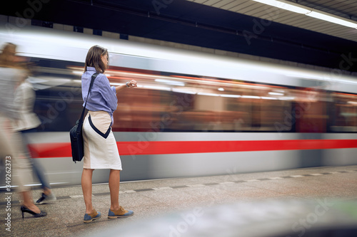 businesswoman in subway looking at her wrist watch. Time goes by fast concept