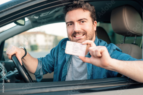 Fotografía Cheerful man holding driver license in his car