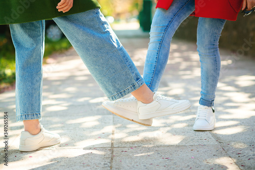 Fototapeta Girls greeting with feet outdoors. Friends on a walk during coronavirus epidemic. Covid-19 concept. Coronavirus prevention. obraz