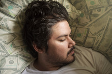 An Unshaven Mixed Race Man Sleeping On A Bed With Dollar Print Pillows. In Deep REM Sleep, Possibly Dreaming.