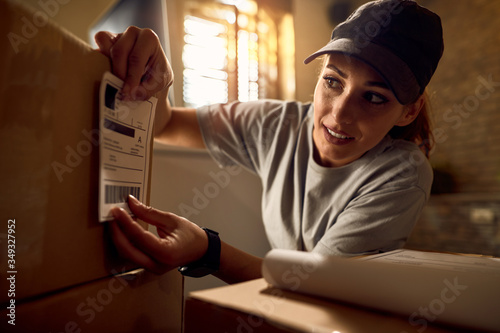 Female courier attaching address label on a package while working in the office Canvas Print