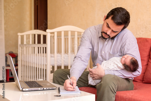 Photo Multitasking father working from home: man sitting in front of laptop, talking on phone, rocking infant baby and writing something in note book