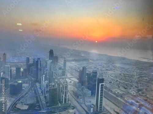 Buildings In City Seen Through Burj Khalifa During Sunset Fotobehang