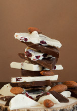 White And Dark Chocolate Is Stacked On Top Of Each Other On A Log Cut, Almonds Are Scattered Around