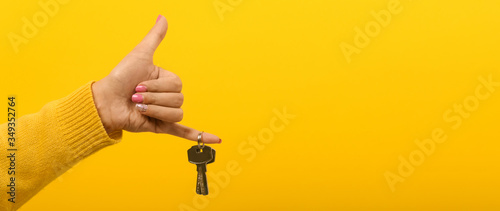 Fotografía hand holding house keys over yellow background, panoramic mock-up