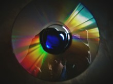 Reflection Of Man On Compact Disc While Photographing Camera