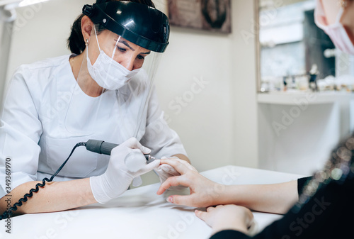 Fototapeta Professional manicure master in Transparent Safety Face Shield using Electric Nail Polisher Tool for Glazing treatment manicure procedure. Small business existence at COVID-19 lockdown concept. obraz