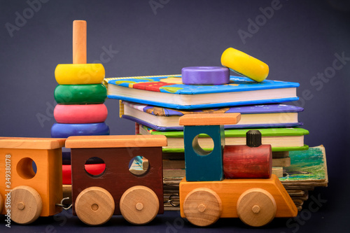 Fun education at home or in school, study, read, learn, and play for perfect academics. Children storybooks, wood toys, puzzle color train standing on dark blue background.
