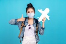 Portrait Of Young Attractive Asian Girl Wear Mask Looking At Camera Show Thumbs Up And Paper Plane In New Next Normal Traveler Concept Come Back Flight Or Return To Fly, Fit To Fly After Reopening.