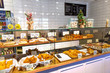 Baked baguettes and pies on showcase in bakery shop. Inscriptions in russian with the name baking