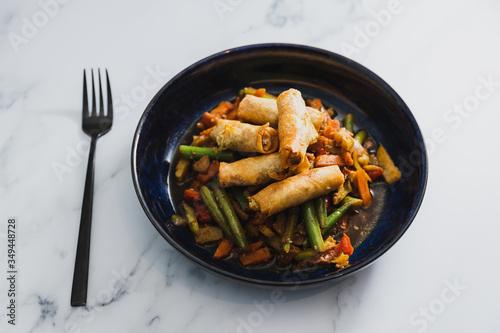 Photo plant-based food, vegan stir fry veggies with spring rolls