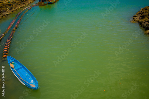MANABI, ECUADOR - JUNE 4, 2012: Small bue boat at stagnant water with a water pu Wallpaper Mural