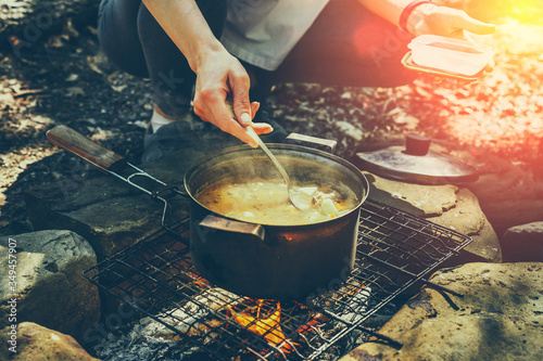 Papel de parede Unrecognizable woman tourist cooking on campfire in forest
