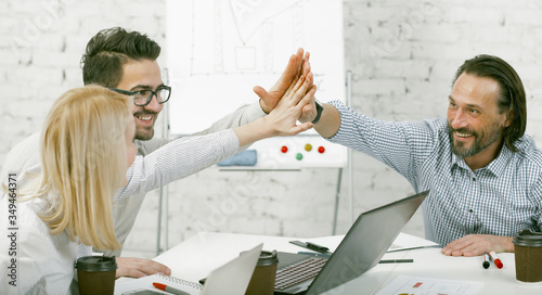 High-five gesture. Colleagues joined their hands in a sign of unity sitting at the desk. Happy business people rejoice at a successful project. Teamwork of business team in office