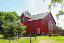 A Bright Red Barn In The Green Field In A Day In Summer