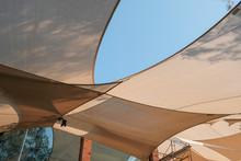Big White Canvas Umbrella With Blue Sky Background. Big White Canvas Roof Background With Clear Sky.