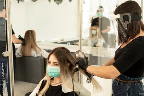 Obraz parrucchiera si accinge ad asciugare con un phon i capelli di una di una cliente all'interno di un salone. Entrambi sono equipaggiati di protezioni per evitare contatti e contaminazioni reciproche - fototapety do salonu