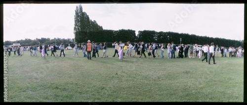 Fototapeta Large Group Of People Walking In Line In Field obraz