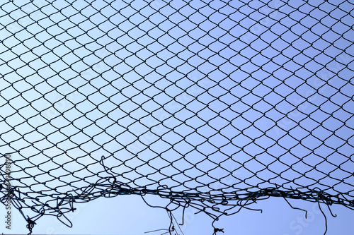 damage wire mesh with blue sky background Fotobehang