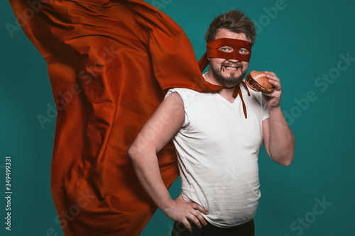 Hungry super hero man eating a hamburger, super hero or antihero in a red suit with a flying cloak eats fast food looking at the camera Fototapet