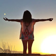 Rear View Of Young Woman With Arms Outstretched Enjoying Sunset