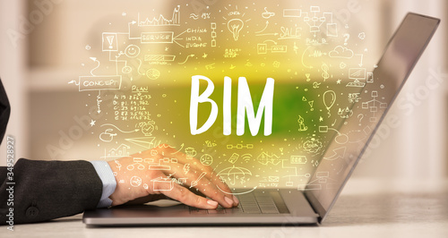 Photo hand working on new modern computer with BIM abbreviation, modern technology con
