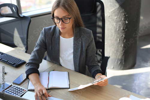 Fényképezés Attractive business woman holding documents and looking at them while sitting at