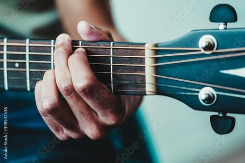 Fotografija boy's hand strumming the strings on a guitar neck