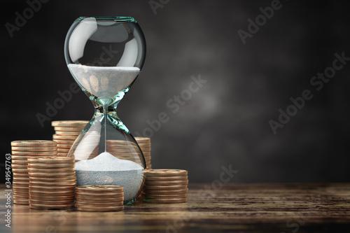 Fotografiet Golden coins and hourglass clock